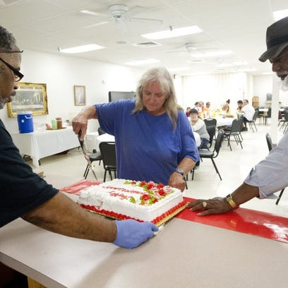 Susan Snow cuts the anniversary cake, assisted by soup kitchen volunteers Michael Sneed, Sr. (left) and the Rev. Iziar Lankford (right) at the Southwest Drive United Methodist Church soup kitchen Tuesday.