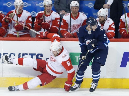 Winnipeg Jets' Tyler Myers (57) checks Detroit Red Wings' Justin Abdelkader (8) during the first period of an NHL hockey game Friday, March 2, 2018, in Winnipeg, Manitoba. (John Woods/The Canadian Press via AP)