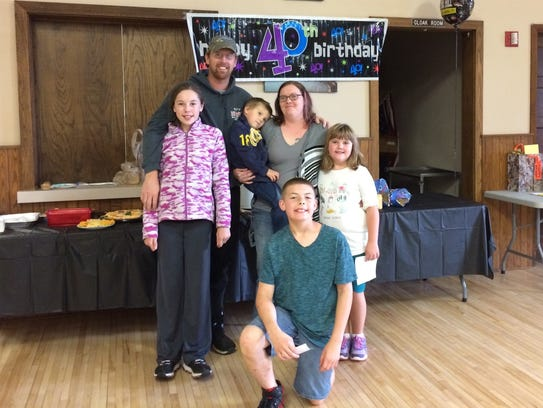 Andy Stuth poses with his children Randon, Zoey, Kaylee
