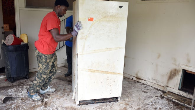 Volunteer Jordan Smith helps move a refrigerator on Wednesday in a house on East 9th Street after flood waters entered a home last week.  Americorps volunteers has helped clean damaged houses from the severe flooding that swept through the Pine Belt.