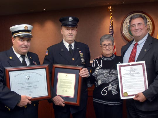 "Union County Freeholder Alexander Mirabella, right, presents a resolution to Nelson ""Rocky"" Carle, second from left, of Roselle Park, congratulating him on celebrating 50 years of active service with the Roselle Park Fire Department. Firefighter Carle was joined by his wife, Lillian. Roselle Park Fire Chief Joseph Signorello also presented Carle with awards."
