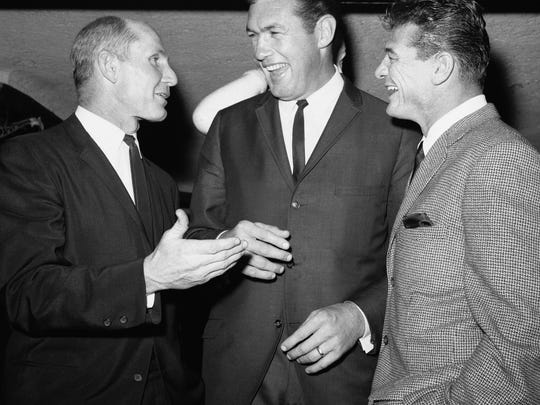 FILE- In this Nov. 18, 1963, file photo, New York Giant quarterback Y.A. Tittle, left, and Giants offensive halfback Hugh McElhenney, right, talk with San Francisco tackle Bob St. Clair, center, as they attend football luncheon in New York. St. Clair, the five-time Pro Bowler who played all 11 of his seasons with his hometown San Francisco 49ers, died Monday, April 20, 2015. He was 84. (AP Photo/Harry  Harris, File)