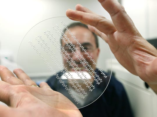 Science teacher at Red Creek High School Joe Bonanno looks at a glass wafer during a tour at Sydor Optics.