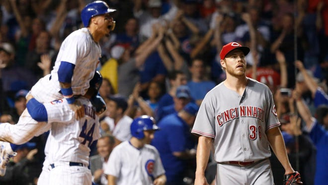 Chicago Cubs' Javier Baez is lifted by Anthony Rizzo (44) after Baez scored the game-winning run on a wild pitch from Cincinnati Reds' Blake Wood, right, during the ninth inning of a baseball game Wednesday, Aug. 16, 2017, in Chicago. The Cubs won 7-6. (AP Photo/Charles Rex Arbogast)