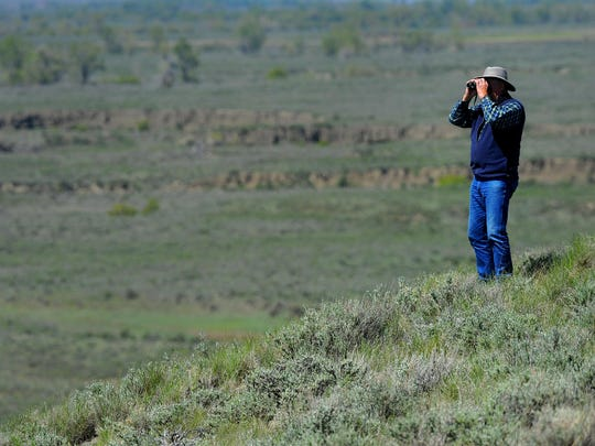 A visitor to the American Prairie Reserve scans the horizon for wildlife in 2015.