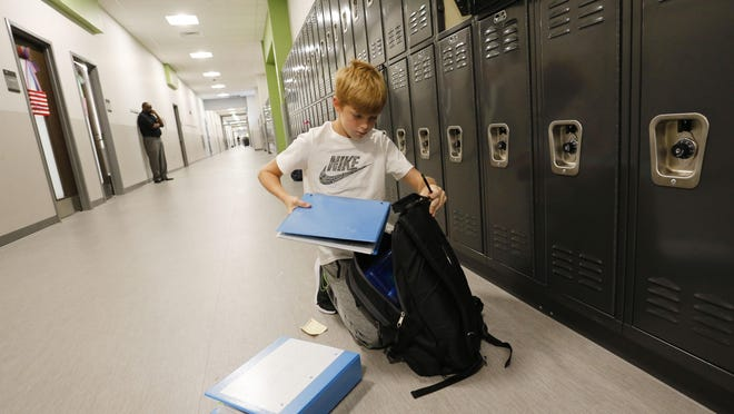 Sipsey Valley Middle School student Randall Frederick organizes his locker and his backpack on Aug. 7, 2019.
