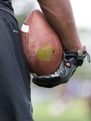 High school football prospects go through drills and