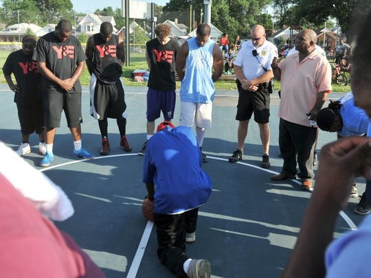 JASON CLARK / COURIER & PRESS Local young adult basketball players are joined by members of the Evansville Police Department as they say a prayer during a previous Together We Will Stop the Violence Dust Bowl Basketball Tournament at Bellemeade Park. The event was part of a community partnership with local community group Young and Established and the Evansville Police Department.