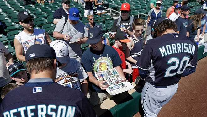 Seattle Mariners' D.J. Peterson, left, and  Logan Morrison (20) sign autographs for fans prior to the spring training exhibition baseball game against the Colorado Rockies Tuesday, March 10, 2015, in Scottsdale, Ariz.