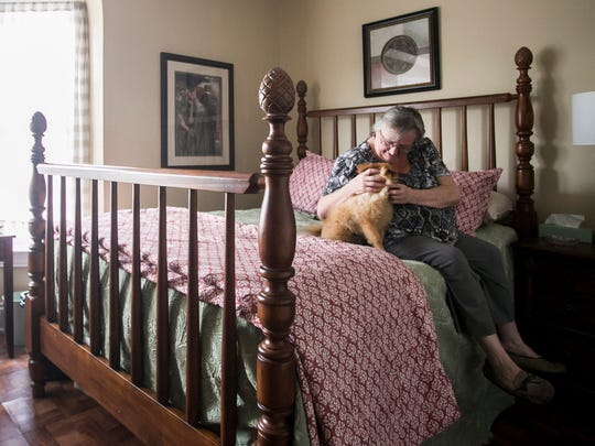 Veteran Deb Gilbert sits on her new bed with her 8-year-old