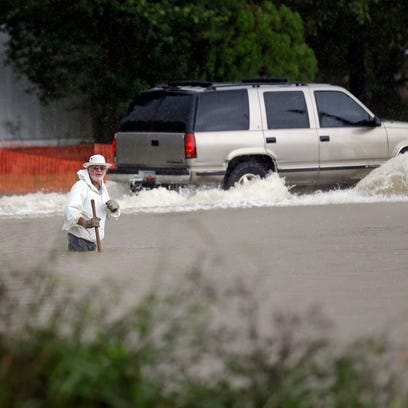 Floodwaters rise as a vehicle and a man navigate flooded