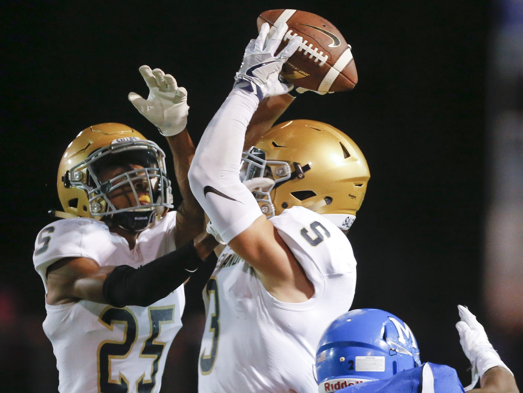 Salesianum's Mike Drake snags a pass intended for Middletown's Kedrick Whitehead in the second quarter at Cavalier Stadium Friday. Salesianum's Desmond Bagley also defends (left).