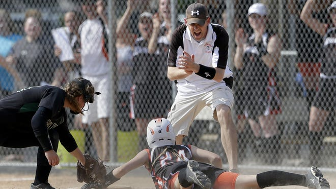 Kaukauna coach Tim Roehrig celebrates along with the dugout behind him as the Ghosts' Sidney Miller makes it safely to third base on a play that allowed Rachel Ashauer (not pictured) to score the only run of their game against Oshkosh North on Monday in Kaukauna. See more pictures at postcrescent.com.
