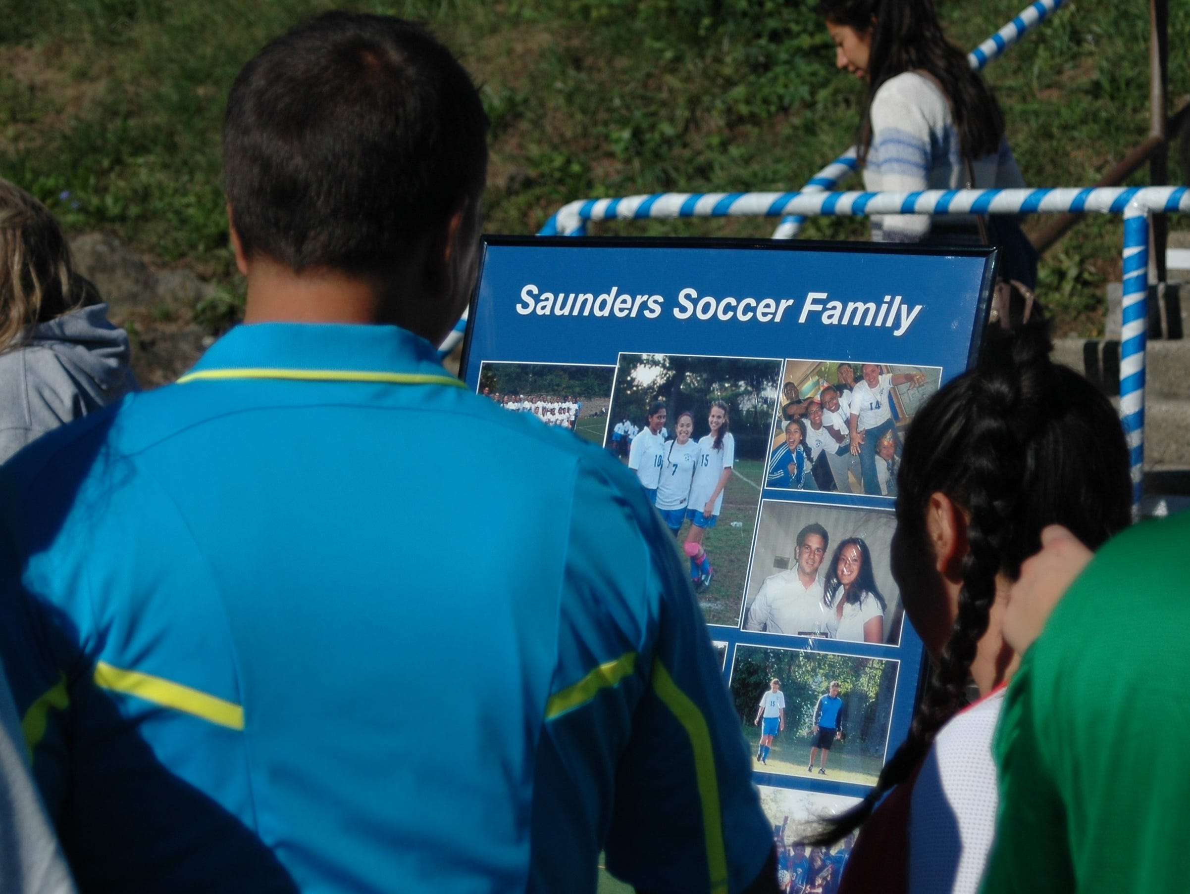 Longtime Saunders girls soccer coach Carlo Mitrione views a framed collection of pictures made by his former players during the school's annual alumni soccer game on Saturday, October 10th, 2015.
