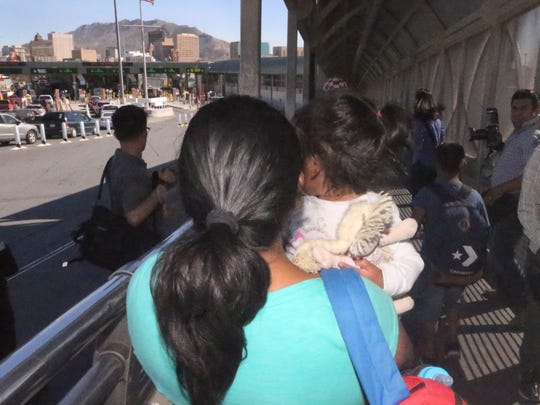 An asylum seeker from Mexico is led to the Paso Del Norte Bridge in El Paso with a small child in tow Wednesday. U.S. Customs and Border Protection officials led two women and their children who were seeking asylum into the port of entry.