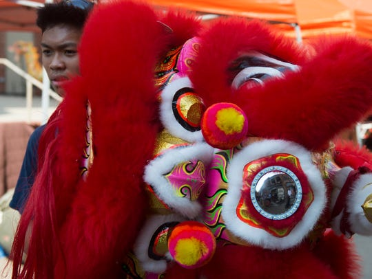A Vietnamese lion dancer prepares to perform at the