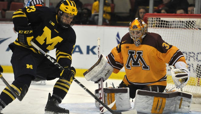Michigan's Alex Kile works in front of Minnesota goalie Adam Wilcox in the first period.  Minnesota won 4-2 to win the Big Ten tournament Saturday at Joe Louis Arena.