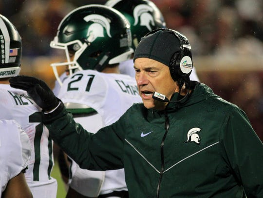 Michigan State coach Mark Dantonio congratulates players