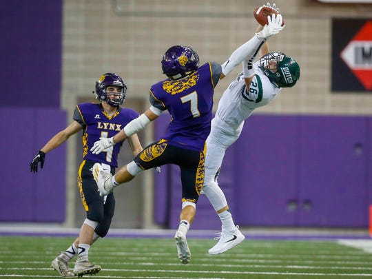 Pella senior wide receiver Ryan Van Wyk (No. 26) reaches to pull in a reception as Webster City junior safety Zane Williams (No. 7) applies pressure on Thursday, Nov. 17, 2016, during the 2016 Iowa high school Iowa Class 3A football championships at the UNI-Dome in Cedar Falls.