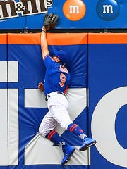 New York Mets center fielder Brandon Nimmo (9) leaps but cannot come up with a solo home run by San Diego Padres catcher Austin Hedges (not pictured) during the fifth inning at Citi Field.
