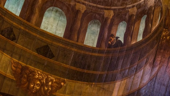 A figure peers from a dome in the trompe l'oeil ceiling.