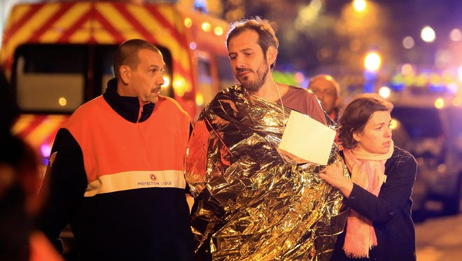 A man is evacuated from the Bataclan theater in Paris after a mass-shooting terrorist attack on Nov. 13, 2015.