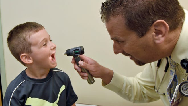 Dr. Micheal Colli peers into the mouth of patient Scott Eshleman, 6, during a routine examination Thursday, June 16, 2016 in a Keystone Health office. Scott does not have hand, foot and mouth disease, but it does strike children in his age group and younger most often, with symptoms that last about a week.