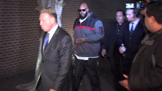 """This image from video shows Death Row Records founder Marion """"Suge"""" Knight, right, walking into the Los Angeles County Sheriffs department early Friday morning Jan. 30, 2015 in connection with a hit-and-run incident that left one man dead and another injured."""