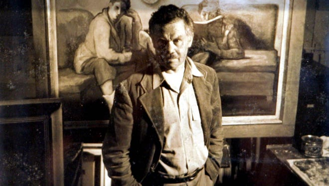 Artist Henry Varnum Poor posed for a portrait with one of his paintings at his home.