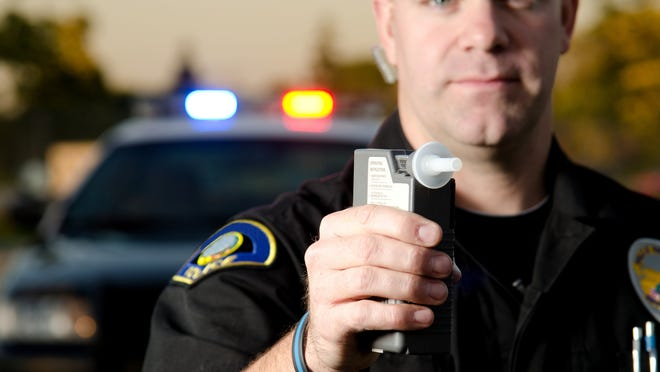 A police officer holding up a Breathalyzer device, with his police vehicle in the background.
