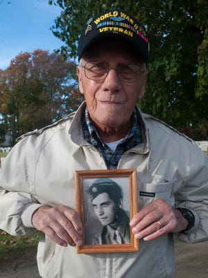 World War II vet Vincent Lobascio show a photo of himself during World War II after a visit to the grave of fellow soldier Anthony Ferri, both, originally from the same Camden neighborhood.