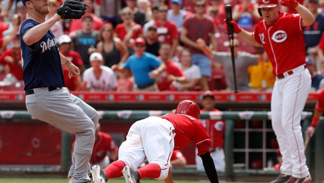 Cincinnati Reds center fielder Billy Hamilton slides safely into home after a passed ball by Milwaukee Brewers relief pitcher Will Smith to win the game in the ninth inning at Great American Ball Park. Reds right fielder Jay Bruce watches at right.