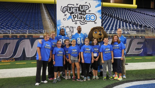 """Highland Elementary students and staff posed for a photo during """"Fuel Up to Play 60 Rally for School Health"""" at Ford Field. Pictured are fifth grade teacher Traci Bradlely, physical education teacher Sherry Bell, Detroit Lions running back Joique Bell, former Lions wide receiver Herman Moore, Roary the Lion, former Lions kicker Jason Hanson, students Jacen Chambers, Trinity Frye, Asia Ramirez, Ashlynn Barriager, Megan Hotchkiss, Jack McIntyre and third grade teacher Jamie Page."""