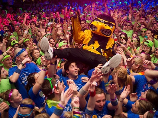 Herky, the University of Iowa mascot, moves across a sea of participants Saturday in the 20th annual U of I Dance Marathon. The student-run charity, which is one of the largest in the nation, raised a record $1.8 million for young cancer patients at the U of I Children?s Hospital.  TIM SCHOON, UNIVERSITY OF IOWA/Special to the Register