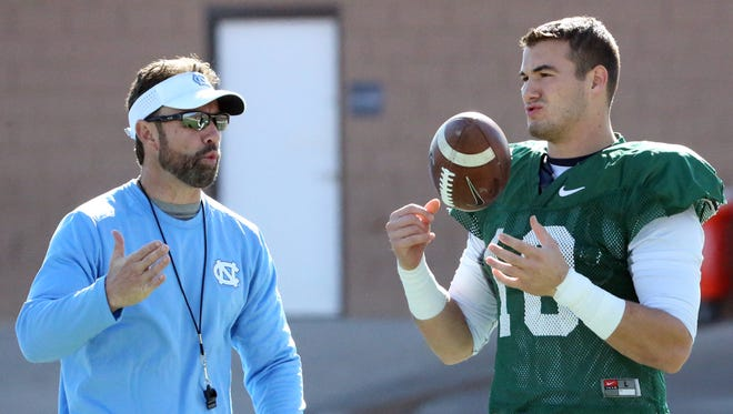 North Carolina head coach Larry Fedora, left, talks with quarterback Mitch Trubisky, 10, at the start of the Tar Heels practice Monday at the Socorro Student Activities Complex.