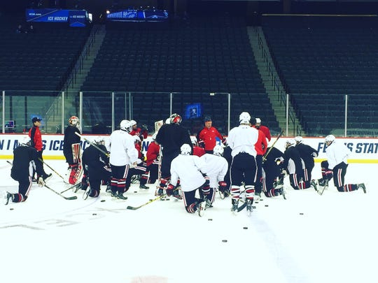 St. Cloud State men's hockey coach Bob Motzko (center, in red and baseball cap) talks to his team during practice Friday at Xcel Energy Center in St. Paul. The Huskies are playing in their fourth straight NCAA tournament Saturday and for the 12th time overall in nationals.