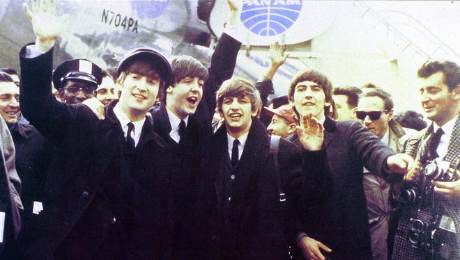 The Beatles - from left, John Lennon, Paul McCartney, Ringo Starr, George Harrison - wave to the crowds at JFK Airport as they arrive for their first U.S. visit on Feb. 7, 1964.