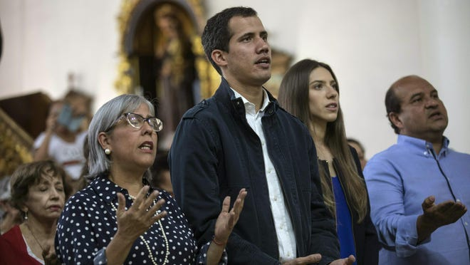 Opposition National Assembly President Juan Guaido, who declared himself interim president of Venezuela, prays next to his wife Fabiana Rosales, second from right, during Mass at a church in Caracas, Venezuela, Jan. 27, 2019. Guaido says he is acting in accordance with two articles of the constitution that give the National Assembly president the right to hold power temporarily and call new elections.