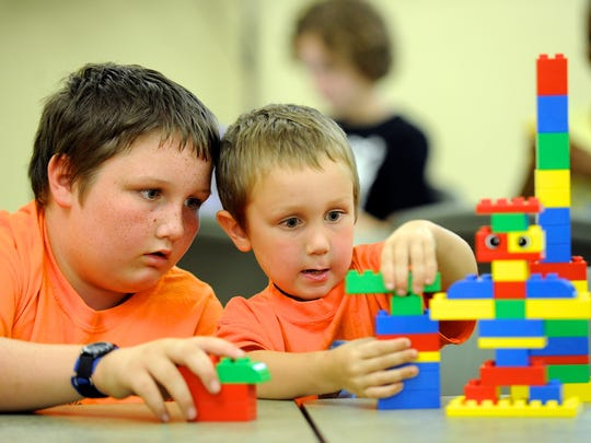 Tucker Skaggs, 4, right, intently works on his structure as his brother, Devon Skaggs, 11, guides his progress during the Duplo Club at the Henderson County Public Library during a past summer program.