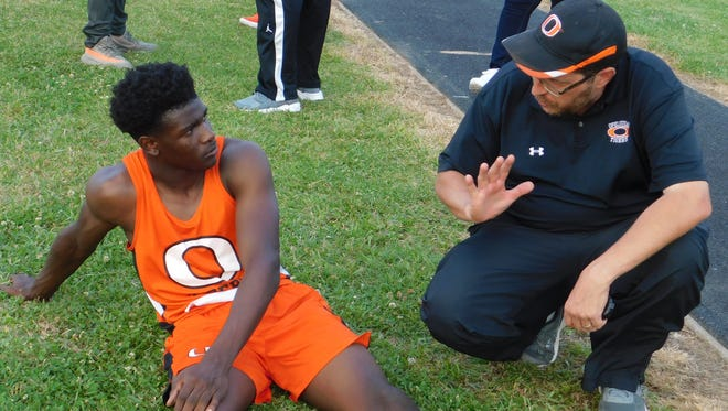 Opelousas High boys' track coach Brock Shaheen counsels an athlete during Tuesday's St. Landry Parish Track Meet at North Central.