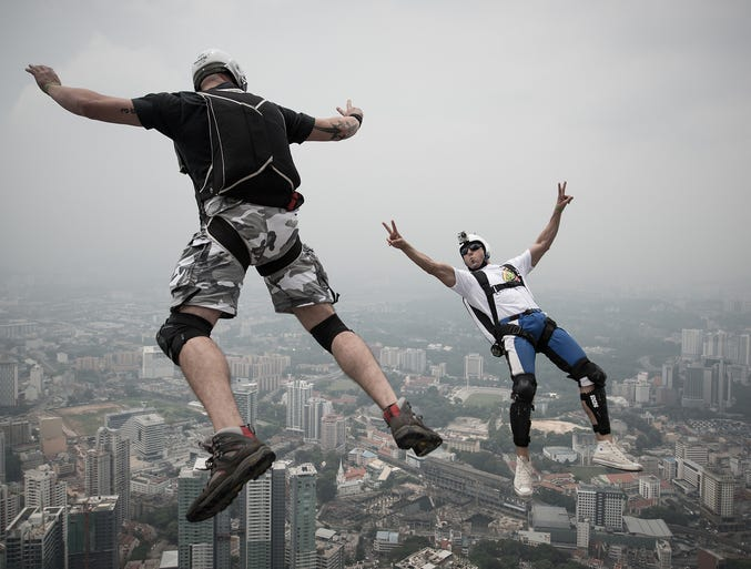BASE jumpers Vladimir Spigler, left, and Ivan Colella leap from the 984-foot Open Deck of Kuala Lumpur Tower during the International Tower Jump event on Sept. 27 in Malaysia. The word BASE stands for building, antenna, span and earth.