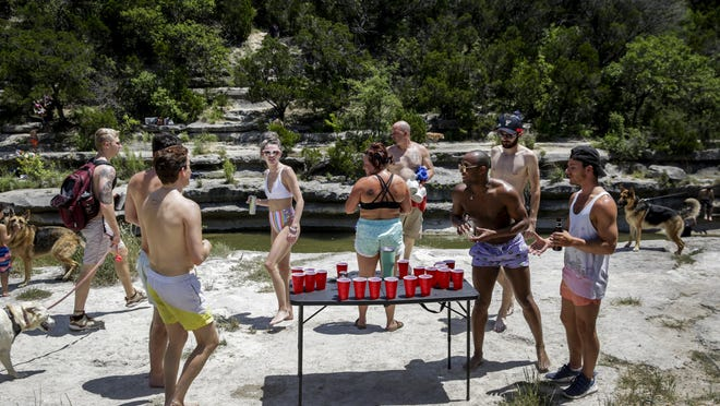 A group of people play beer pong at watering hole on Bull Creek off of Loop 360 on May 2, soon after Gov. Greg Abbott launched the first phase of his plan to reopen the state. Austin health officials on Wednesday said people taking fewer precautions to prevent the spread of the coronavirus are part of the reason for a recent increase in cases.