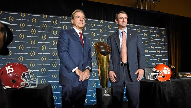 Clemson head coach Dabo Swinney and Alabama head coach Nick Saban pose with the National Championship trophy after their head coaches press conference Sunday, January 10, 2016 in Scottsdale, AZ.