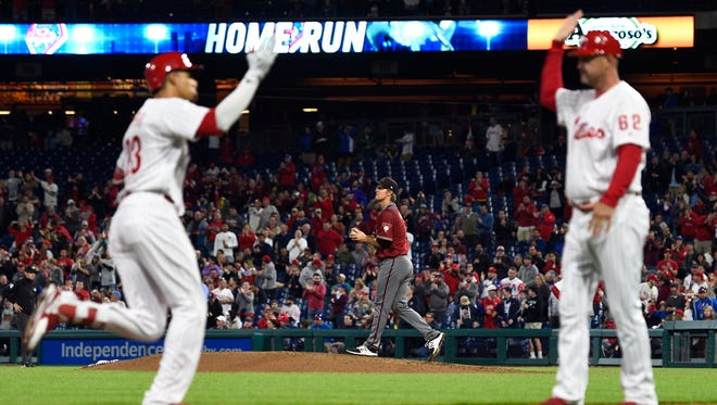 Arizona Diamondbacks starting pitcher Zack Greinke, center, walks back to the mound after giving up a three-run home run to Philadelphia Phillies' Aaron Altherr (23) during the sixth inning of a baseball game, Wednesday, April 25, 2018, in Philadelphia. The Phillies won 5-3.