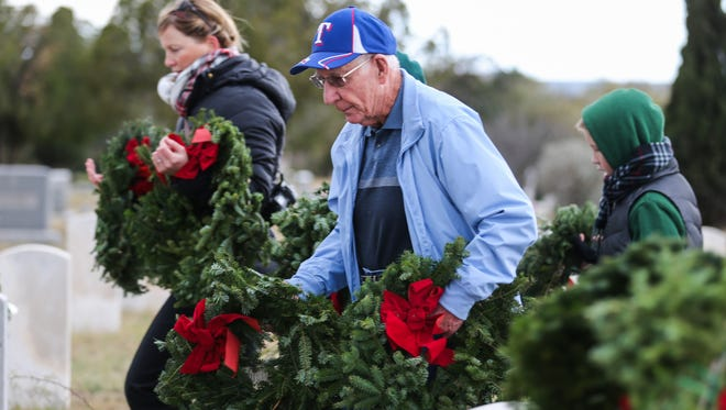 Participants lay wreaths on graves during the Wreaths Across America ceremony Saturday, Dec. 16, 2017, at Belvedere Memorial Park Cemetery.