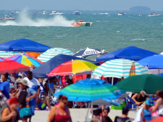 Thousands pack the shore of Cocoa Beach as offshore powerboats maneuver their way through rough waters during Sunday afternoon's Thunder on Cocoa Beach Space Coast Super Boat Grand Prix .