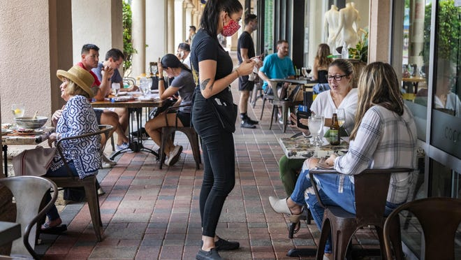 Customers dine outside at Kapow Noodle Bar in Mizner Park in Boca Raton, Florida on May 15, 2020.
