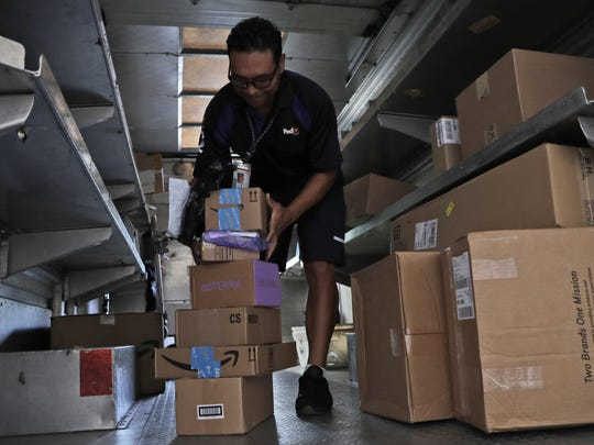 In this July 17, 2018, file photo, a FedEx employee delivers packages in Miami. Outside of ditching online shopping altogether, there are some small tweaks in how you shop that can cut down on the impact on the environment, such as slowing down shipping times and not filling up the cart with stuff you know you won't keep.