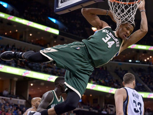 Milwaukee Bucks forward Giannis Antetokounmpo (34) hangs from the rim after dunking the ball in the first half of an NBA basketball game against the Memphis Grizzlies, Monday, March 13, 2017, in Memphis, Tenn. (AP Photo/Brandon Dill)