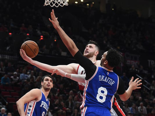Portland Trail Blazers center Jusuf Nurkic drives to the basket and scores on Philadelphia 76ers center Jahlil Okafor during overtime of an NBA basketball game in Portland, Ore., Thursday, March 9, 2017. The Blazers won 114-108. (AP Photo/Steve Dykes)
